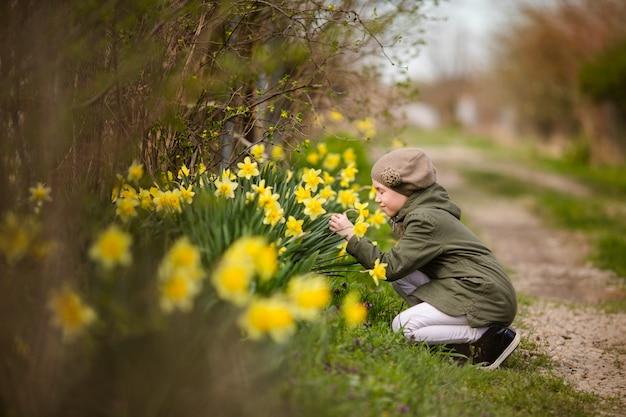 Adolescente en veste verte et béret kaki près du jardin des jonquilles à la campagne.