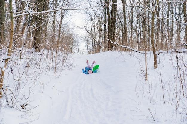 Une adolescente vêtue d'un chapeau rose et d'un manteau bleu essaie de se déplacer sur un traîneau vert depuis une glissade de neige