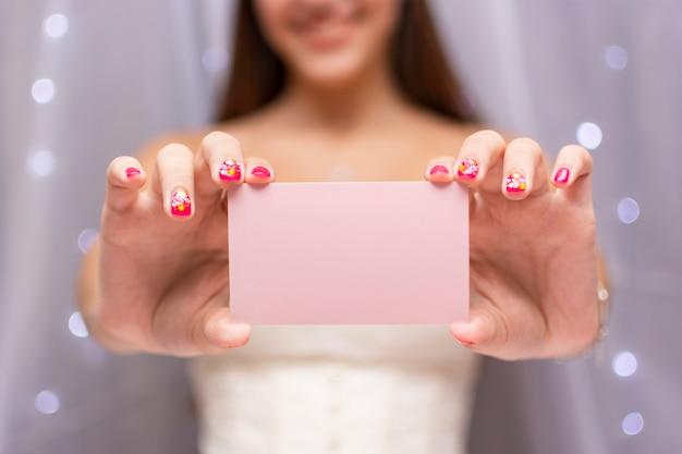 Adolescente vue de face tenant une carte d'anniversaire rose