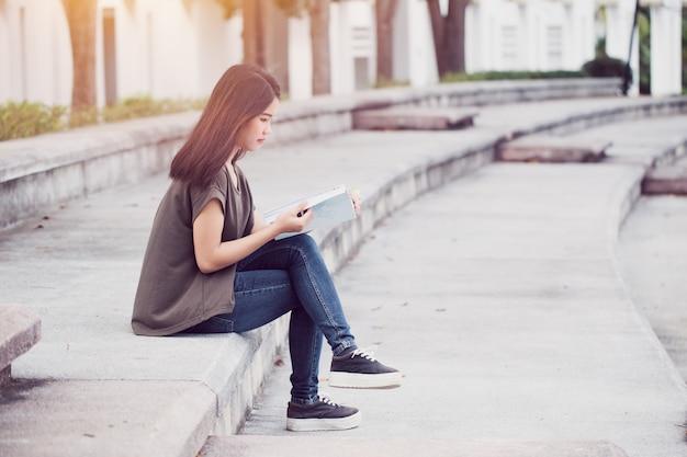 Des adolescentes asiatiques en train de lire des livres sur le bonheur et le sourire