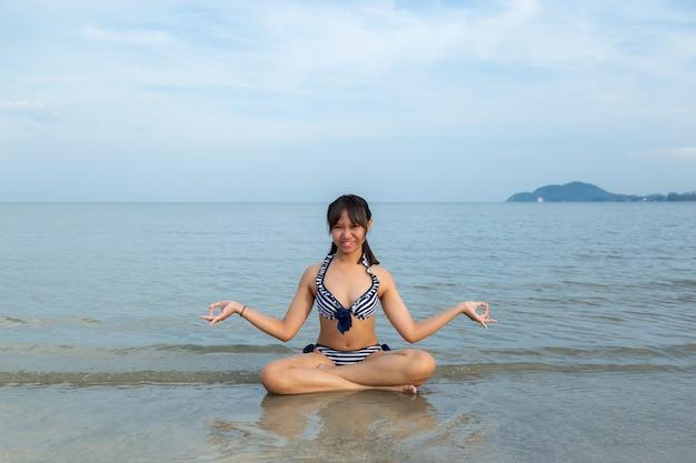 Adolescentes d'asie en bikini assis méditation à la plage.
