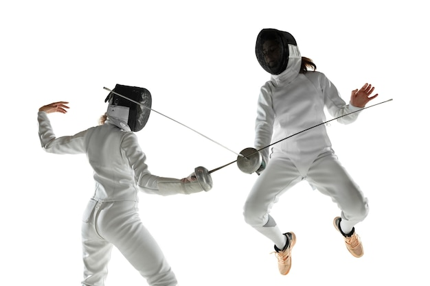 Les adolescentes en costumes d'escrime avec des épées dans les mains isolés sur fond de studio blanc. jeunes modèles féminins pratiquant et s'entraînant en mouvement, action. copyspace.