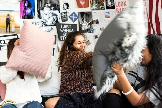 Adolescentes dans une chambre à coucher ayant un oreiller lutte soirée pyjama et concept de l'enfance