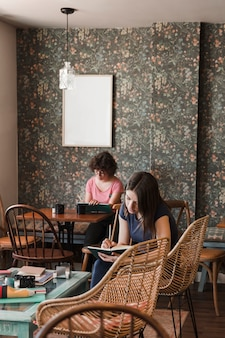 Adolescentes, écrivant dans des cahiers au café