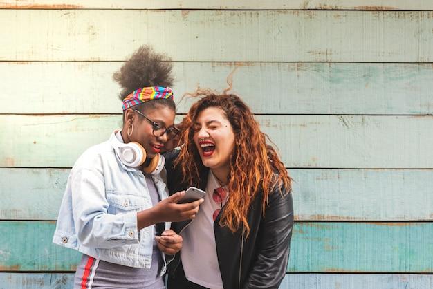 Adolescentes multiraciales utilisant un téléphone portable à l'extérieur.