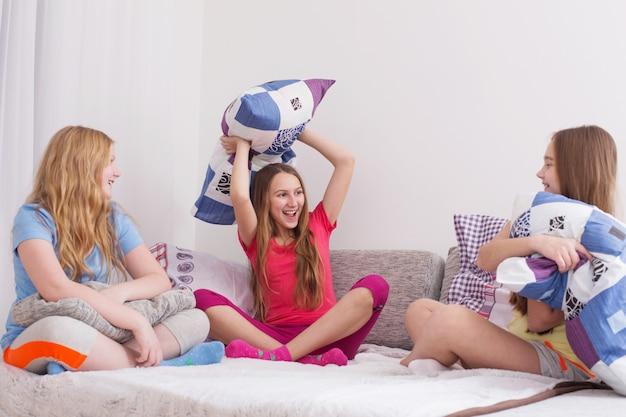 Adolescentes s'amusant et se battant avec des oreillers