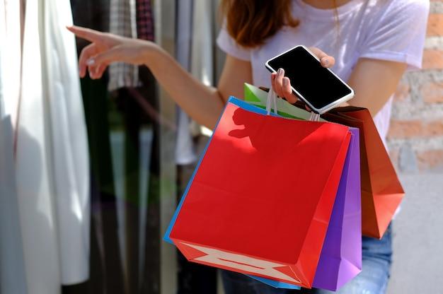 Adolescentes tenant un sac à provisions et un téléphone portable.
