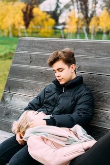 Les adolescents amoureux sont assis sur un banc de parc en automne, discutent joyeusement, discutent.