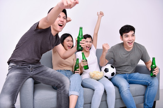 Adolescents asiatiques regardant le football à la télévision