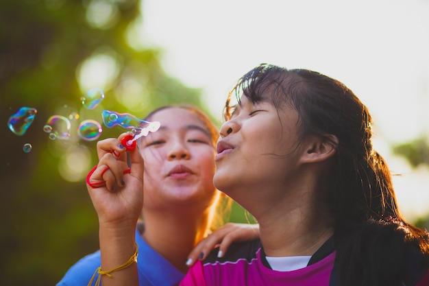 Adolescents asiatiques soufflant des bulles