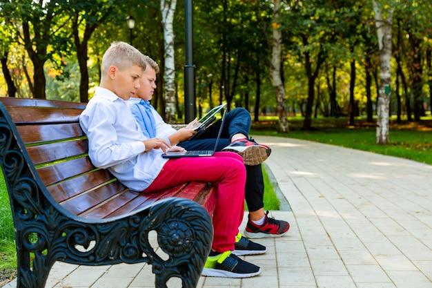 Adolescents sur banc de parc à l'aide d'un ordinateur portable et d'une tablette numérique.