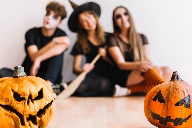 Adolescents en costumes d'halloween assis avec des citrouilles