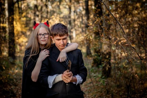 Adolescents en costumes d'halloween dans les bois.