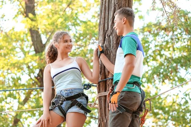Adolescents escalade dans le parc aventure