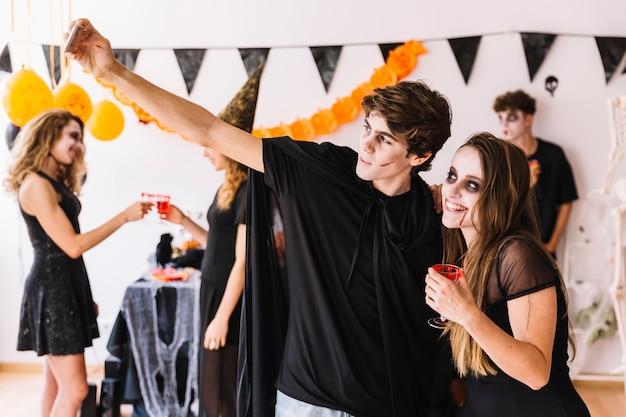 Des adolescents faisant des selfies à la fête d'halloween