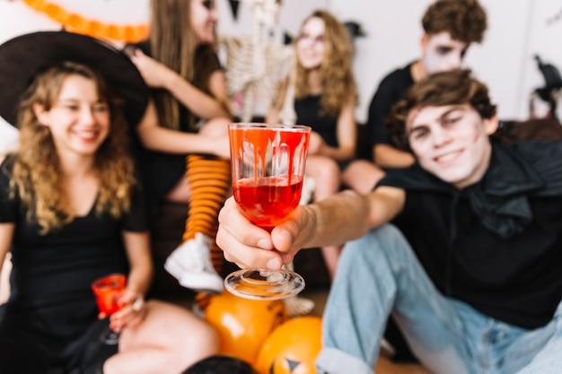 Adolescents à la fête d'halloween buvant des verres avec du sang peint