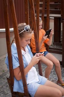 Adolescents avec des gadgets assis sur les balançoires