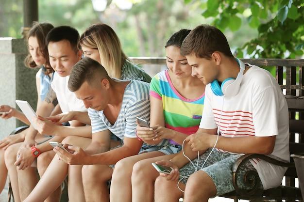 Adolescents avec des gadgets dans la rue