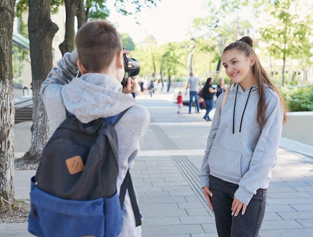 Les adolescents, garçons et filles, se promènent dans la ville et sont photographiés à la caméra. amitié, meilleurs amis