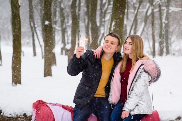 Adolescents heureux célébrant dans la forêt d'hiver