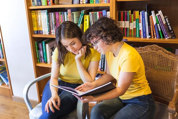 Adolescents intelligents lisant le livre ensemble