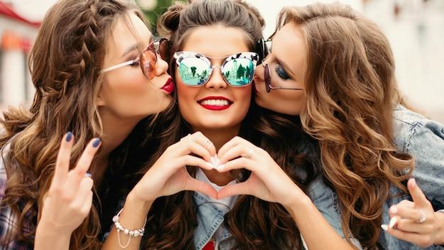 Adolescents magnifiques lunettes de soleil embrassant leur ami souriant avec geste du coeur.