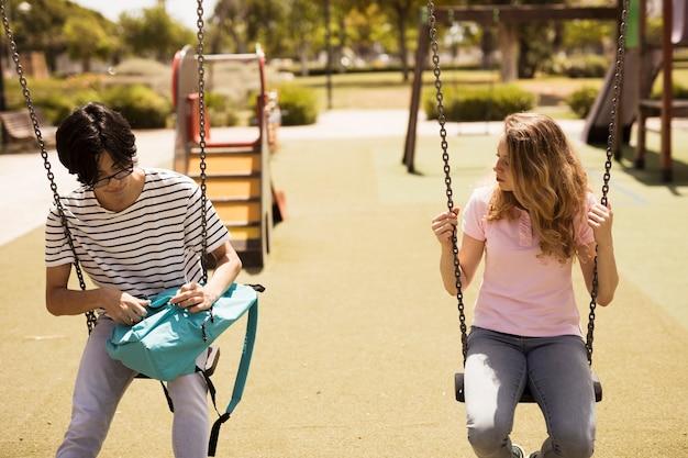 Adolescents multiethniques assis sur des balançoires