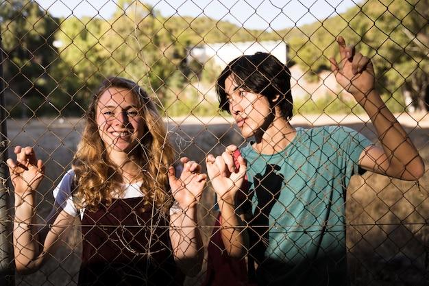 Adolescents occasionnels derrière un fil métallique