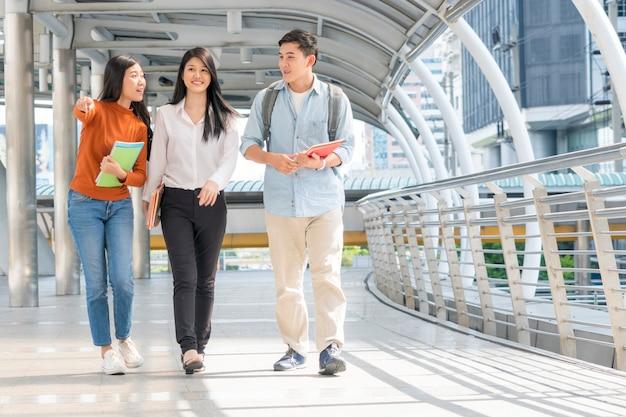 Adolescents optimistes énergiques et femme d'affaires marchent et parlent au public en plein air
