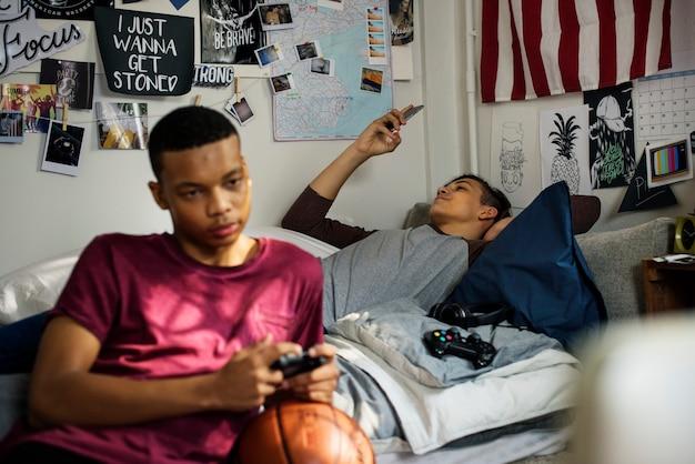 Adolescents traînant dans une chambre à coucher jouant à un jeu vidéo et utilisant un smartphone
