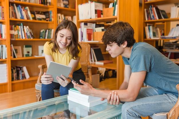 Adolescents utilisant des gadgets dans la bibliothèque