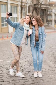 Adolescents vue de face prenant des selfies ensemble