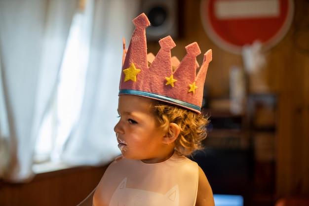 Adorable bambin dans une couronne est assis à la maison dans un bavoir petite princesse avec une drôle d'émotion