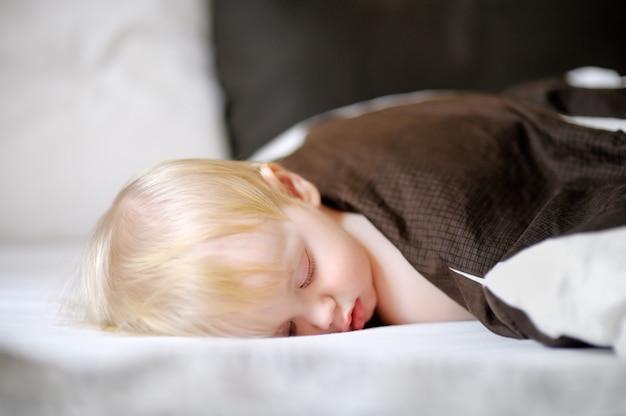Adorable bambin garçon dormant dans un lit