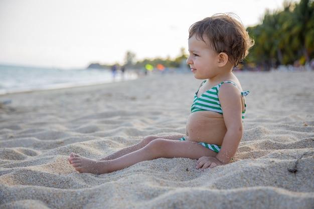 Un adorable bambin en maillot de bain est assis sur une plage tropicale de sable de la mer chaude au soleil.