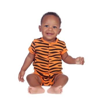 Adorable bébé africain en pyjama avec des brindles assis par terre