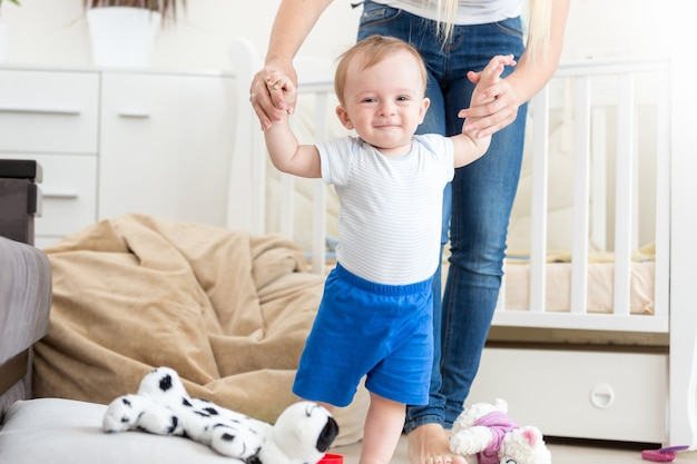 Adorable bébé apprenant à marcher avec sa mère à la maison