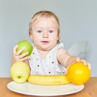 Adorable bébé aux yeux bleus blond tenant une pomme verte et une assiette orange avec des fruits