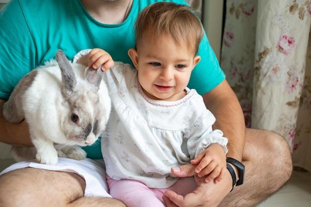 Adorable bébé est assis dans les bras de papas et caresse un lapin décoratif animaux domestiques dans une famille avec