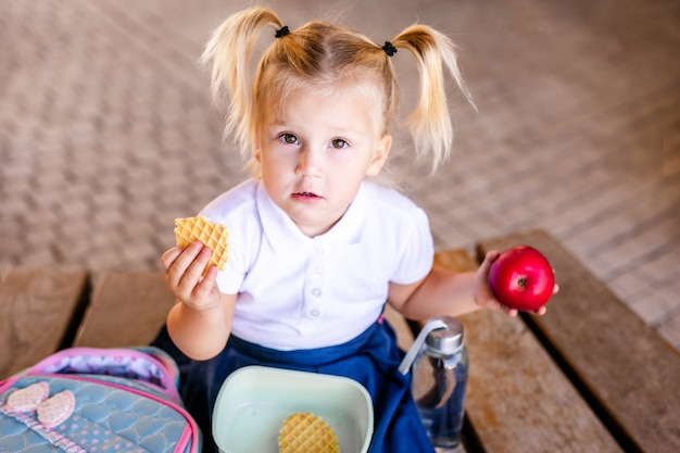 Adorable bébé fille bébé caucasien assis et mangeant