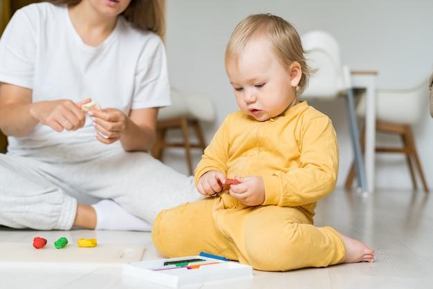 Adorable bébé jouant avec de la pâte à modeler sur une mère sans visage au sol favorisant le développement de l'enfant