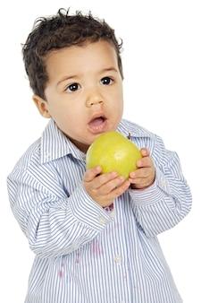 Adorable bébé mange une pomme sur fond blanc