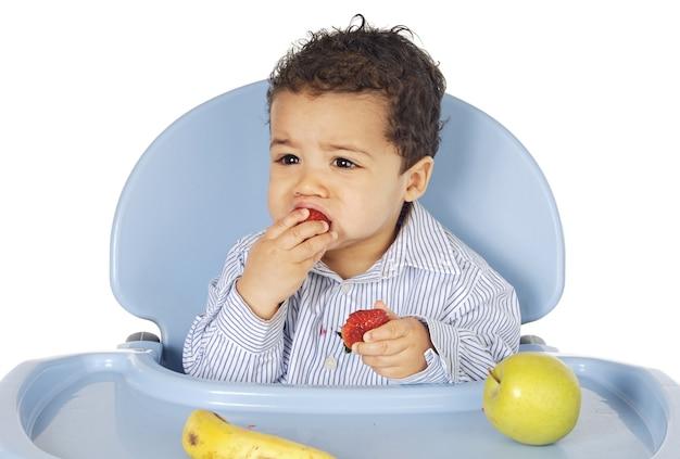 Adorable bébé, manger des fruits sur fond blanc