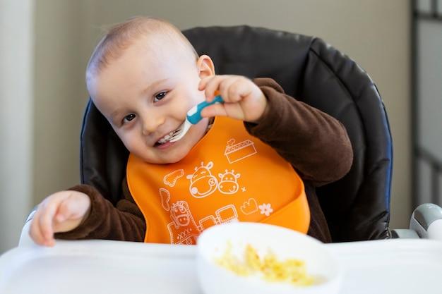 Adorable bébé mignon de 18 mois prenant une fourchette en plastique dans sa bouche et jouant avec de la nourriture