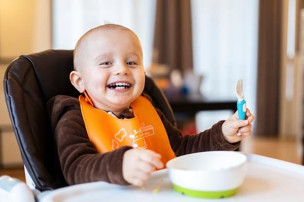 Adorable bébé mignon prenant une fourchette en plastique dans sa main et jouant avec de la nourriture assis dans la chaise haute.