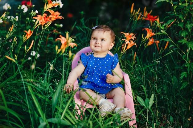 Adorable bébé mignon avec une robe bleue souriant dans un jardin plein de belles fleurs
