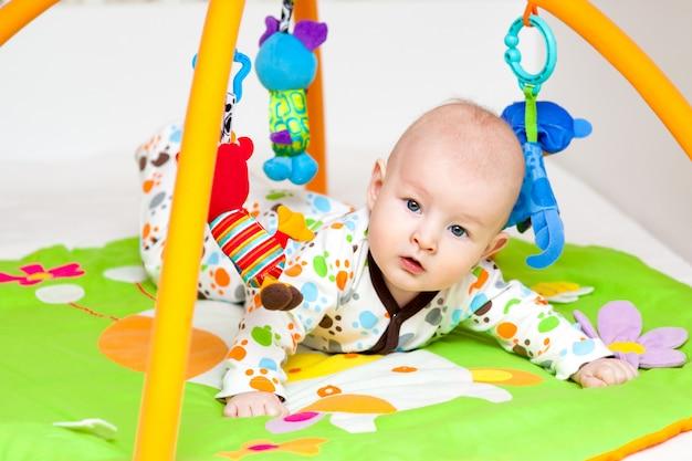 Adorable bébé s'amuser avec des jouets sur tapis de jeu coloré.