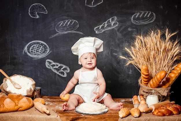 Adorable bébé sur la table avec de la pâte