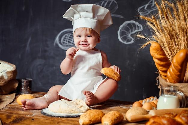 Adorable bébé sur table avec de la pâte