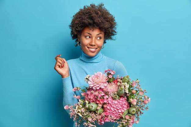 Adorable charmante jeune femme obtient des fleurs comme cadeau d'anniversaire regarde pensivement de côté sourit doucement habillé en poloneck isolé sur mur bleu